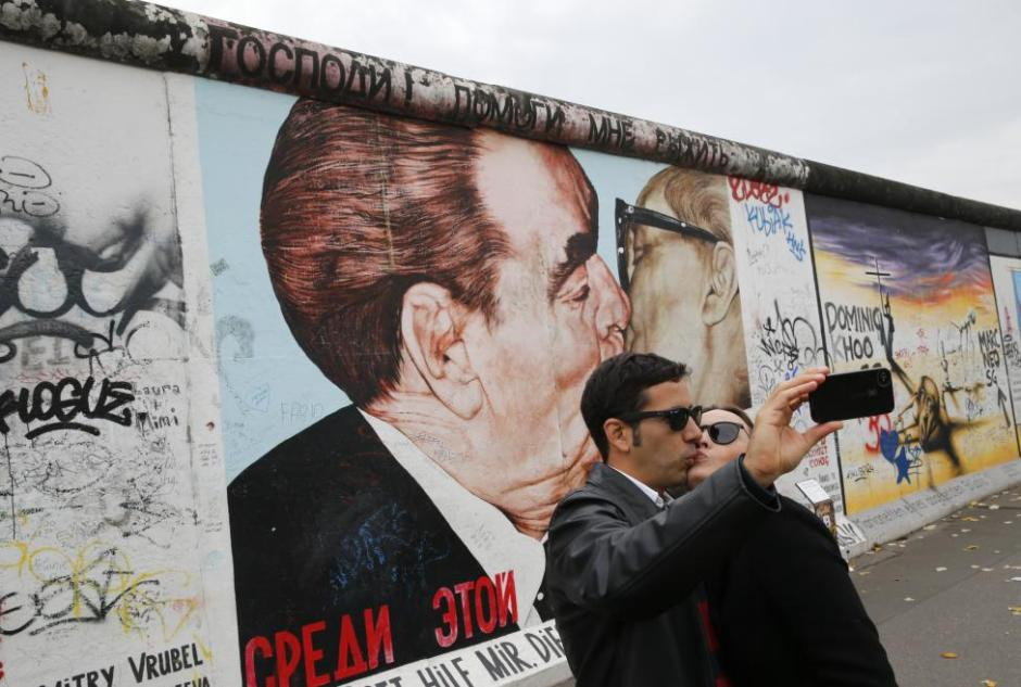 Tourists take pictures with a mobile phone in front of a painting depicting former Soviet leader Leonid Brezhnev kissing his East German counterpart Erich Honecker (R) painted on a segment of the East Side Gallery, the largest remaining part of the former Berlin Wall, in Berlin, November 3, 2014. Germany will celebrate the 25th anniversary of the fall of the wall on November 9. REUTERS/Fabrizio Bensch
