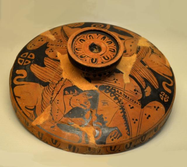 Ερυθρόμορφο κάλυμμα αγγείου Κάλυμμα αγγείου, πιθανότατα πυξίδας ή λεκανίδας, διακοσμημένο με την ερυθρόμορφη τεχνική. Εικονίζονται κεφαλές Αριμασπών ανάμεσα σε γρύπες, παράσταση εμπνευσμένη από τη μυθολογία. Οι Αριμασποί ήταν άγριο πολεμικό γένος του βορρά, που απειλούσε τον ειρηνικό λαό των Ισσηδόνων, ευνοούμενο από το θεό Απόλλωνα. Ο θεός έστειλε στους Ισσηδόνες τους γρύπες για να τους προστατεύσουν από τους Αριμασπούς. Η πάλη Αριμασπών και γρυπών συμβόλιζε την πάλη καλού και κακού και χρησιμοποιήθηκε ως θέμα πολλών παραστάσεων. Ειδικά τον 4ο αι. π.Χ., εποχή μεταφυσικών αναζητήσεων, θέματα με παρόμοιους συμβολισμούς επιλέγονταν συχνότερα στην αγγειογραφία.